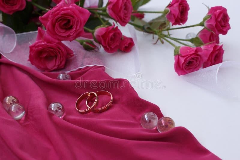 Złociste obrączki ślubne na różowej tkaninie z białymi różami i faborkiem zdjęcie royalty free