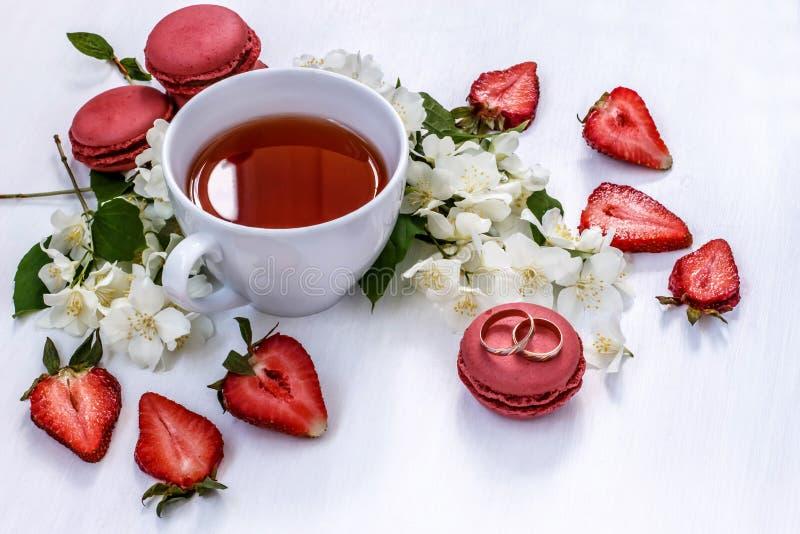 Złociste obrączki ślubne obok filiżanki herbata, macaroons, truskawki i jaśmin, obrazy royalty free