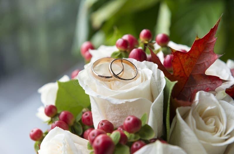 2 złocistej obrączki ślubnej na białej róży w bukiecie zdjęcia stock