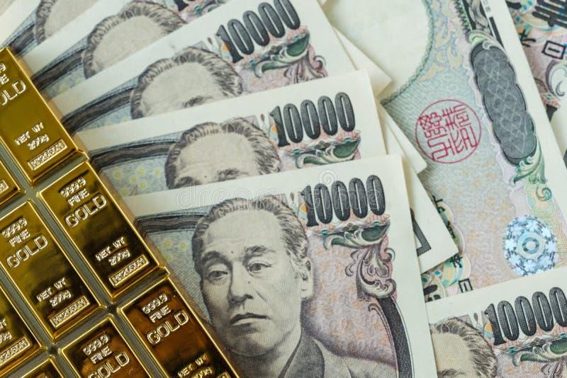 Złocistej sztaby ingot i stos japońskiego jenu banknoty jako financi obrazy royalty free