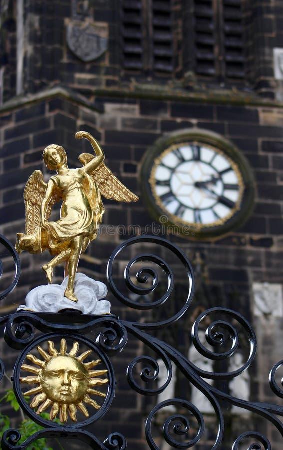 Złocisty anioł Na Kościelnej bramie z Kościelnym zegarem w tle obraz stock