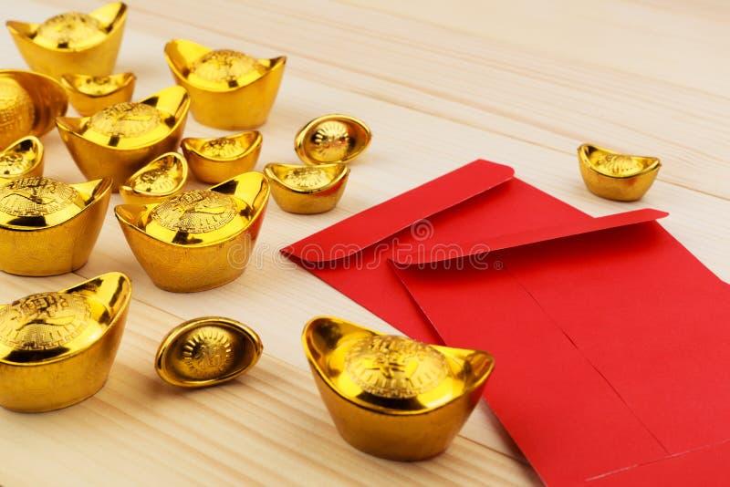Złocisty Chiński ingot i puste miejsce czerwone koperty na drewnianym tle obrazy royalty free