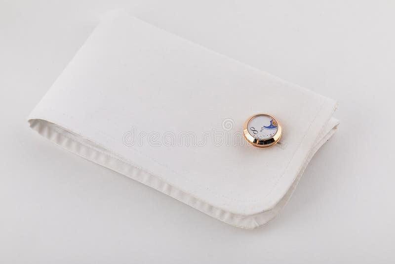 Złocisty cufflink przy mankiecikiem w formie okręgu odizolowywającego na białym tle fotografia stock