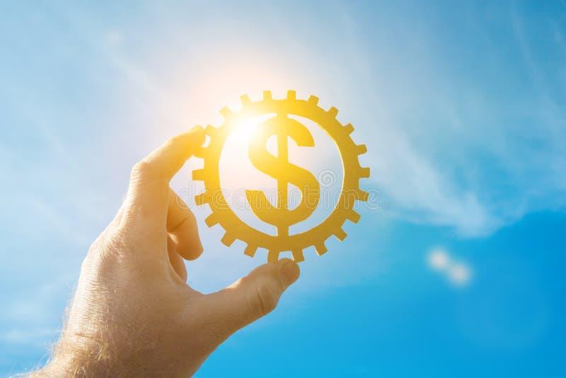 Złocisty dolarowy symbol pieniądze w przekładni trzyma biznesmena ręką zdjęcia stock