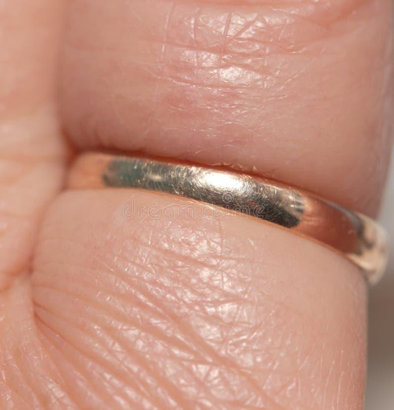 Złocisty pierścionek na jego palcu Makro- fotografia stock