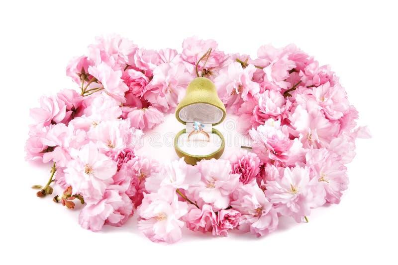 Złocisty pierścionek z błękitnym topazem w prezenta pudełku dla biżuterii w kształcie otaczającym różowymi czereśniowymi kwiatami obraz royalty free