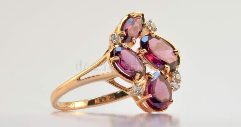 Złocisty pierścionek z rhodolite i zircon wszywkami zdjęcie royalty free