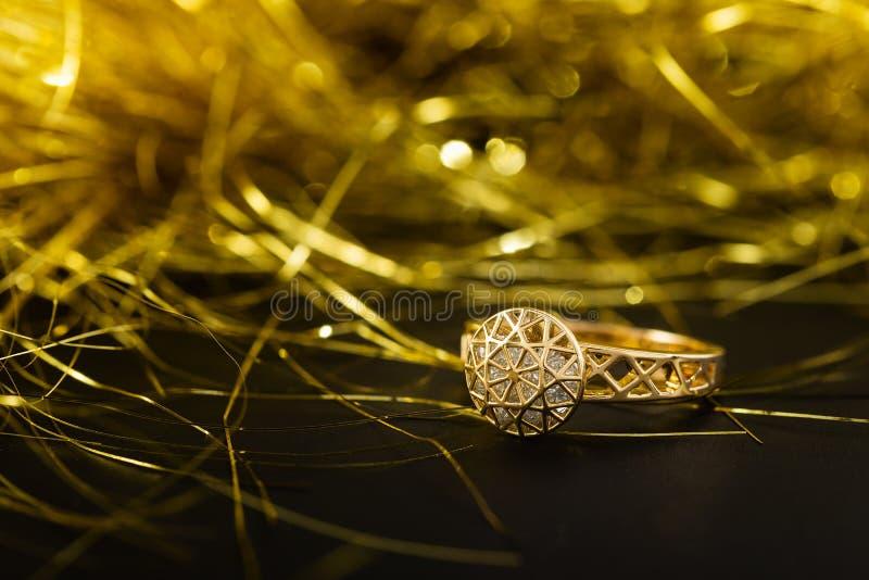 Złocisty pierścionek zaręczynowy z diamentami na czarnym tle obraz royalty free