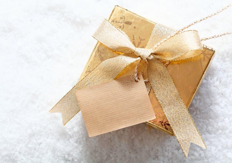 Złocisty prezenta pudełko z pustą etykietką w śniegu obrazy stock