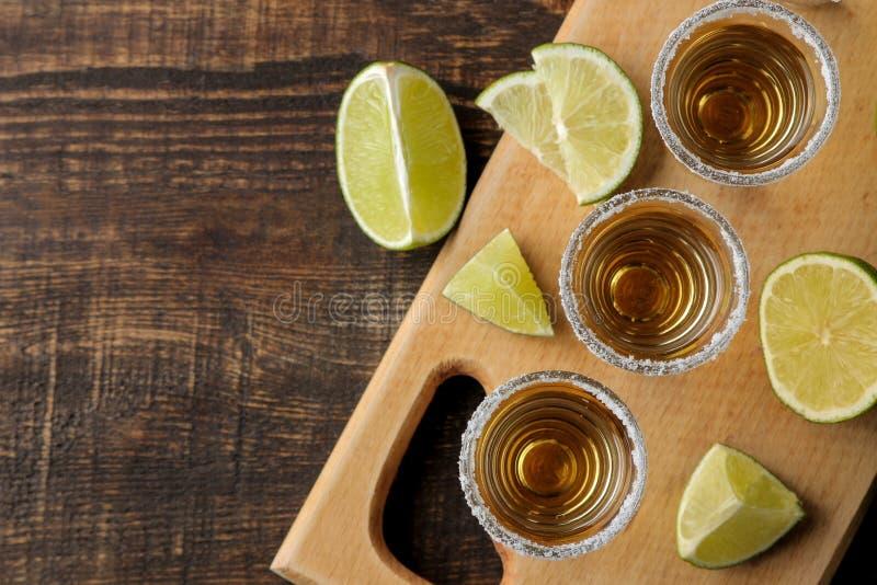 Złocisty tequila w szklanym strzału szkle z solą i wapnem na brązu drewnianym tle Odgórny widok z przestrzenią dla teksta zdjęcia royalty free