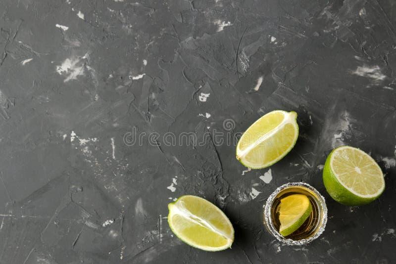 Złocisty tequila w szklanym strzału szkle z solą i wapnem na czarnym betonowym tle bar napoje alkoholowe Odgórny widok z spac fotografia stock