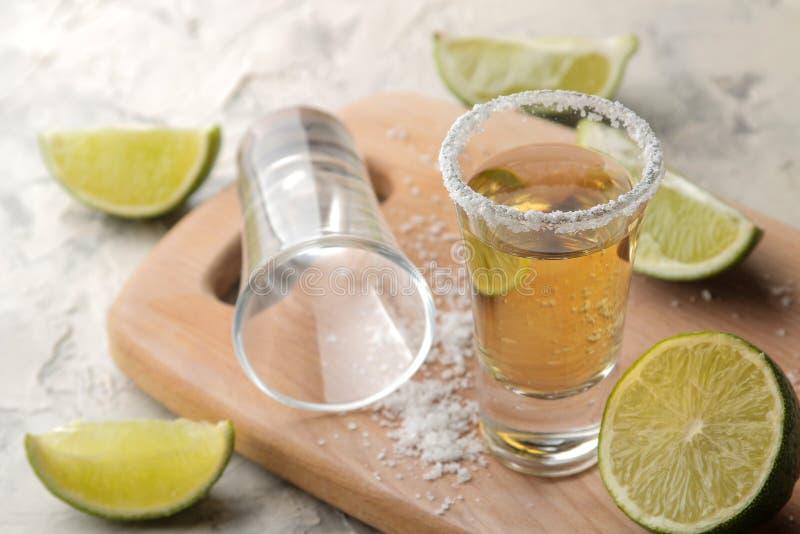 Złocisty tequila w szklanym strzału szkle z solą i wapnem na lekkim betonowym tle bar napoje alkoholowe zdjęcie royalty free