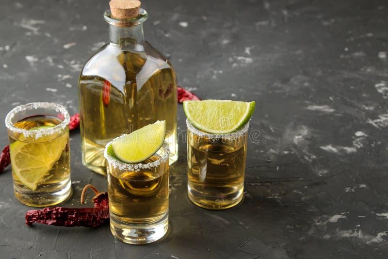 Złocisty tequila w szklanym strzału szkle z solą, wapnem i gorącym pieprzem na czarnym betonowym tle, bar napoje alkoholowe zdjęcia royalty free