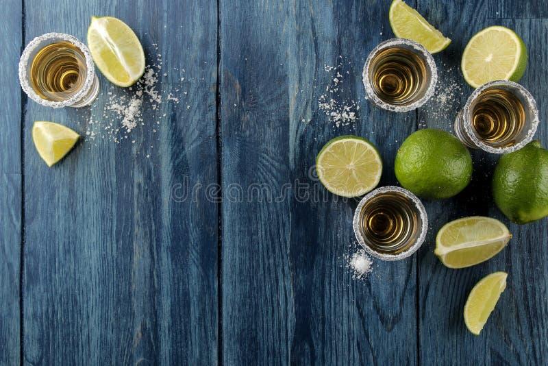 Złocisty tequila w szklanym szkle z solą i wapnem na błękitnym drewnianym tle bar napoje alkoholowe na widok Z przestrzenią obraz stock
