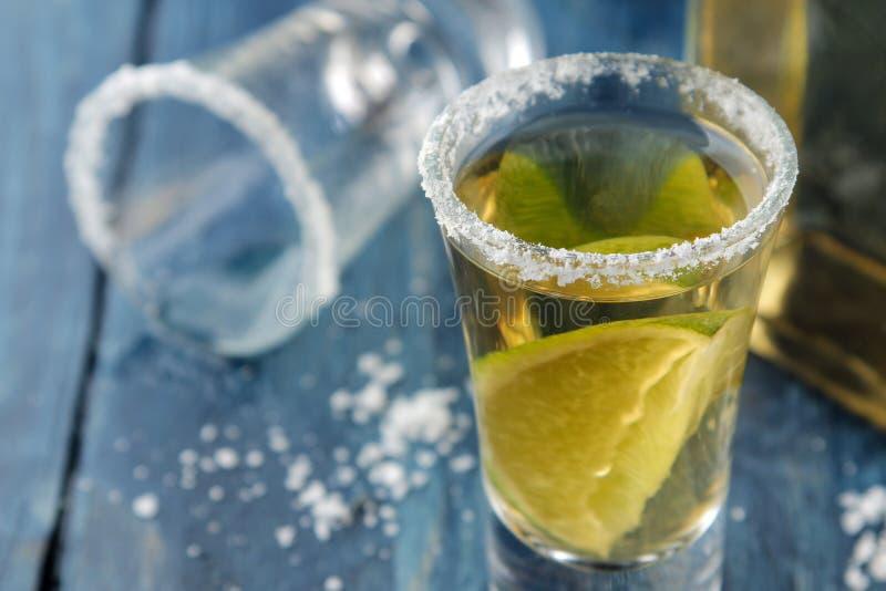 Złocisty tequila w szkle z solą i wapnem na błękitnym drewnianym stole napoje alkoholowe Zako?czenie fotografia royalty free