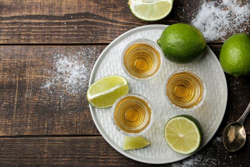 Złocisty tequila w szkle z solą i wapnem na brązu drewnianym stole napoje alkoholowe Odg?rny widok obrazy stock