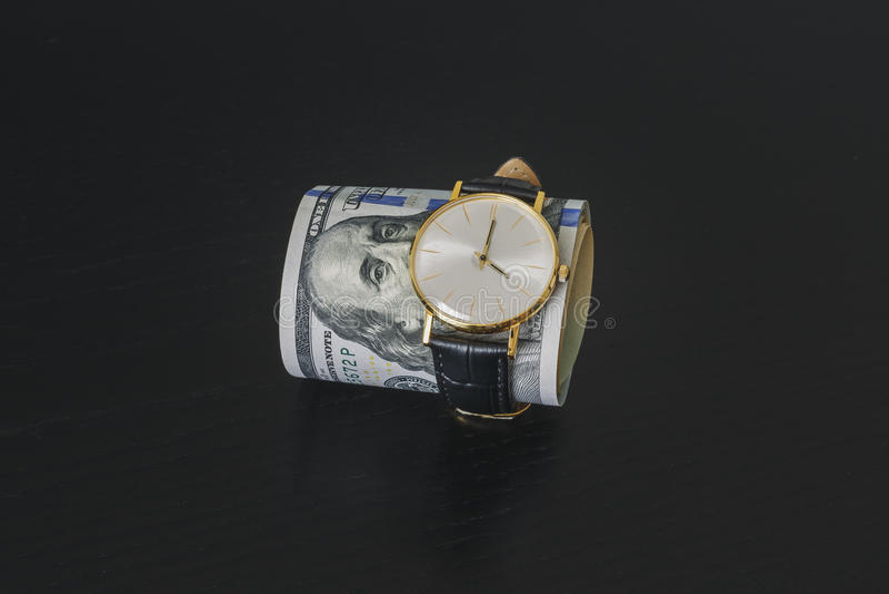 Złocisty zegarek na dolarowych pieniędzy banknotach obrazy stock