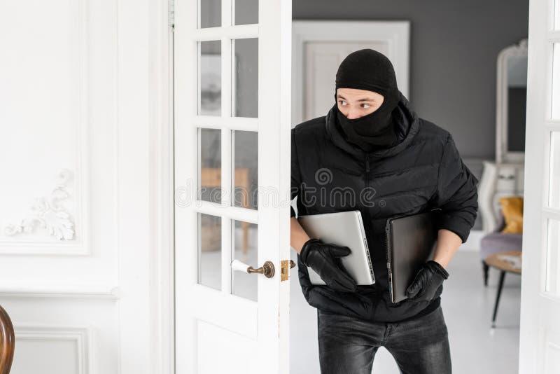 Złodziej kraść dwa nowożytnego drogiego laptopu z czarnym balaclava Włamywacz popełnia przestępstwo w Luksusowym mieszkaniu z zdjęcia stock