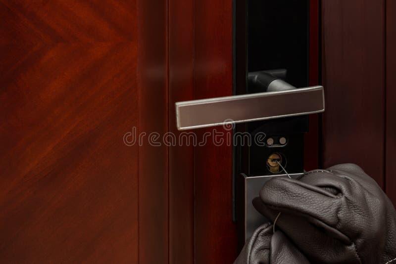 Złodziej otwiera drzwiowego kędziorek obraz royalty free