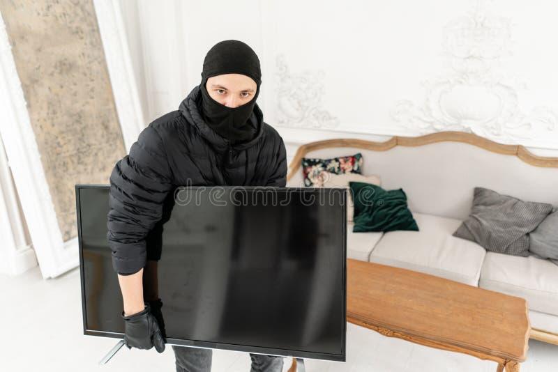 Złodziej patrzeje kamerę z czarnym balaclava kraść nowożytną drogą telewizję, Luksusowy mieszkanie z stiukiem zdjęcia royalty free