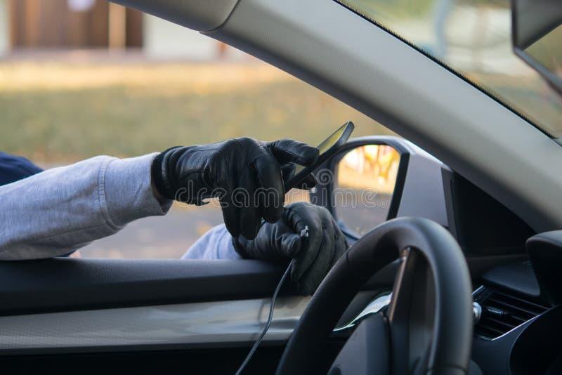 Złodziej ręka w czarnej rękawiczce, bierze smartphone z przodu samochodu, przez otwartego szkła, łama drut zdjęcie stock
