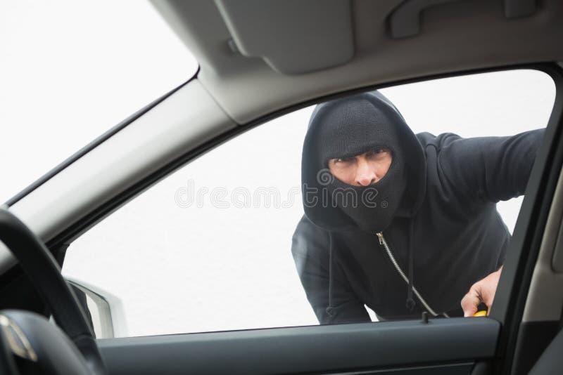 Złodzieja łamanie w samochód z śrubokrętem zdjęcia stock