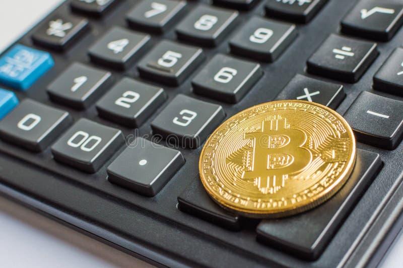 Złota bitcoin moneta na kalkulatora zakończeniu up zdjęcie stock