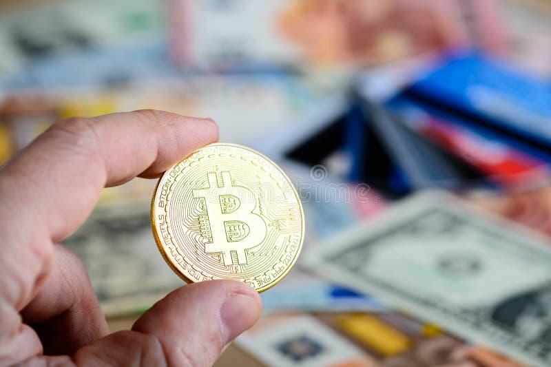 Złota bitcoin moneta w mężczyzna ręce - symbol crypto waluta przeciw zdjęcie royalty free