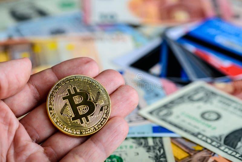 Złota bitcoin moneta w mężczyzna ręce - symbol crypto waluta przeciw fotografia royalty free