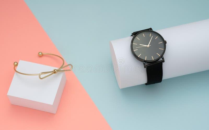 Złota bransoletka z wristwatch na zieleni i różowym pastelowego koloru tle zdjęcie royalty free
