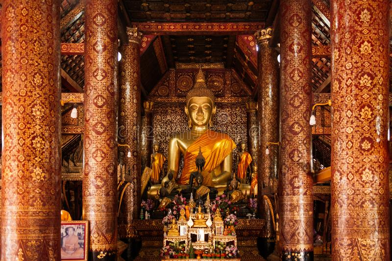 Złota Buddha statuy sala i malowidło ścienne sztuki ściana przy Wata Xieng paskiem Luang Prabang, Laos, - fotografia royalty free