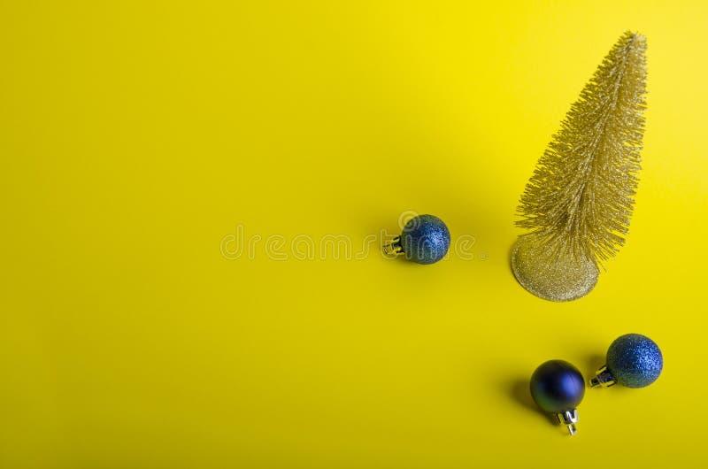 Złota choinka z błękitnymi piłkami na żółtym tle zdjęcie stock