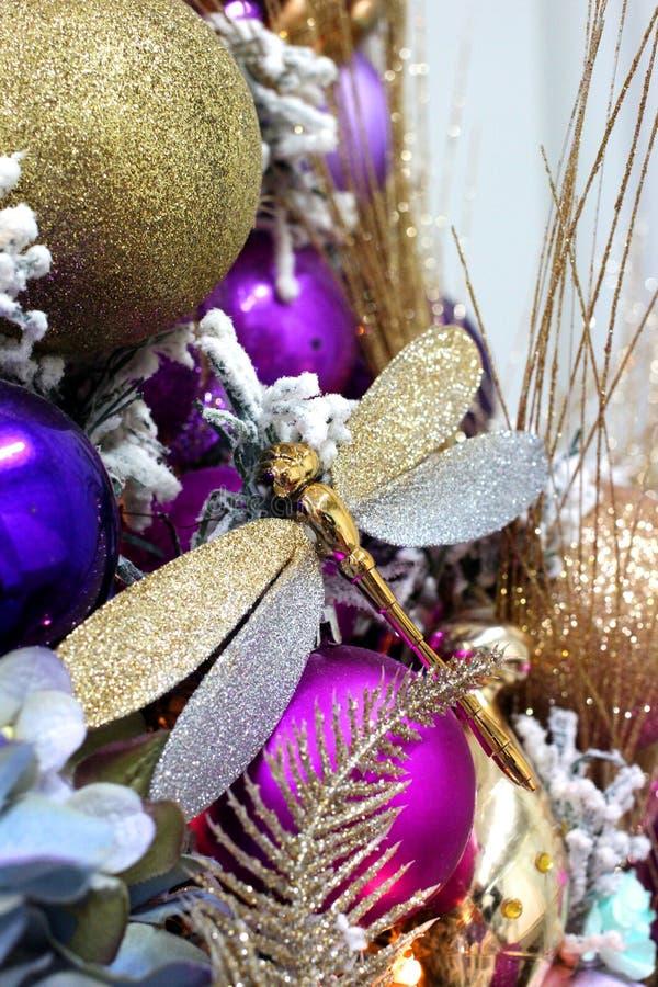 Złota dragonfly choinka z kolorowymi dekoracjami i prezentami w dekoracyjnym wnętrzu dla wakacje zdjęcia stock