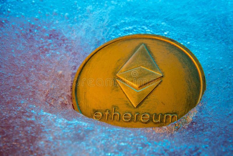 Z?ota Ethereum moneta, online cyfrowa waluta marzn?ca w b??kitnym lodzie Poj?cie blokowy ?a?cuch, targowy trzask Zamarzni?ty cryp obrazy royalty free
