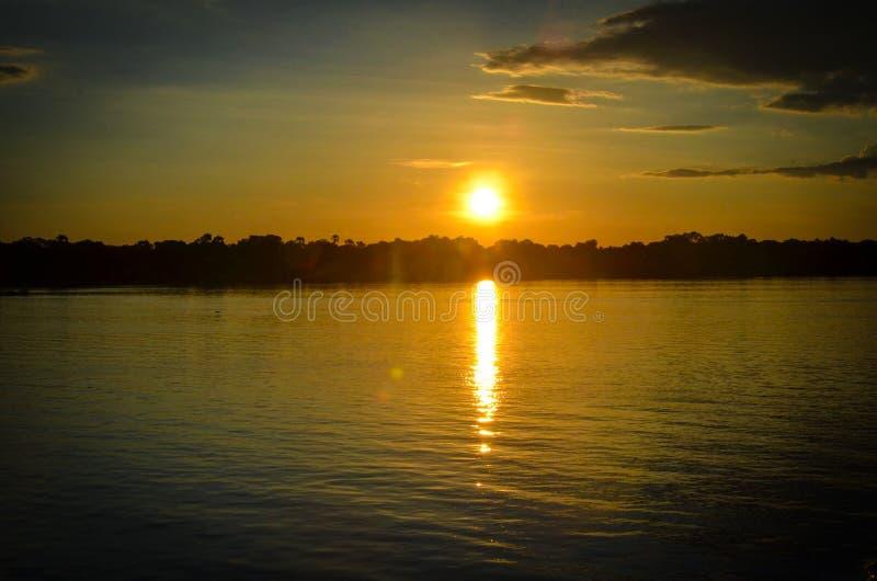 Złota godziny sylwetka nad ogromną rzeką obraz royalty free