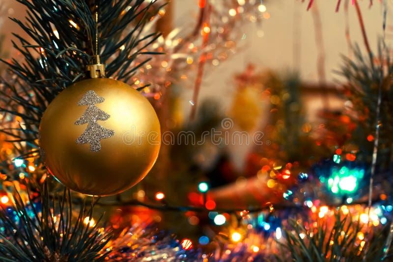 Złota piłka z srebrem malował drzewnego obwieszenie na choince wśród świateł obrazy stock