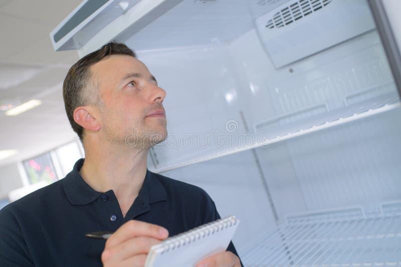 Złota rączka stoi blisko fridge i bierze notatki zdjęcia stock