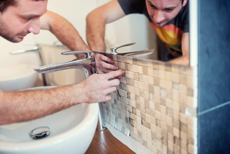 Złota rączka używa adhezyjnego cement dla instalować ceramiczne mozaik płytki Szczegóły odświeżanie zdjęcia royalty free