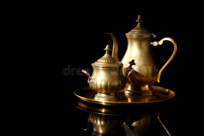 Złota taca z teapot i cukierniczką na czarnym tle obrazy stock