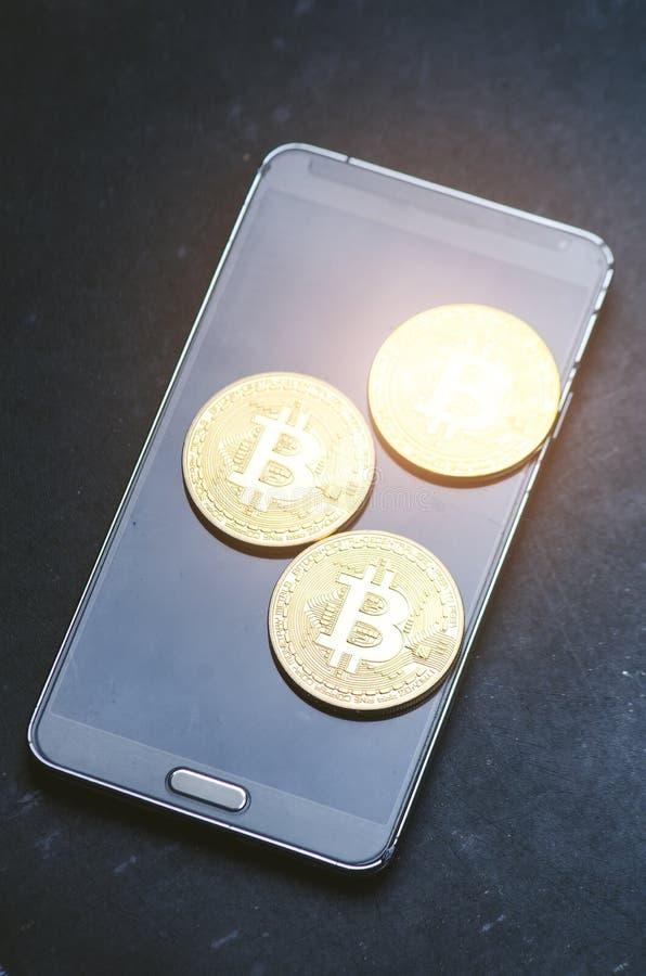 Złote bitcoin monety na mądrze telefonie Wirtualna waluta Crypto waluta nowy wirtualny pieniądze Obiektywu raca obrazy stock