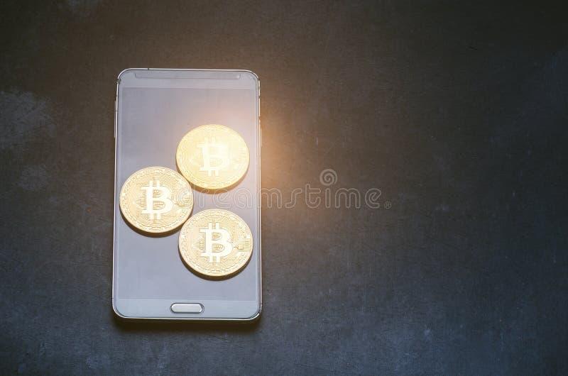 Złote bitcoin monety na mądrze telefonie Wirtualna waluta Crypto waluta nowy wirtualny pieniądze Obiektywu raca obraz stock