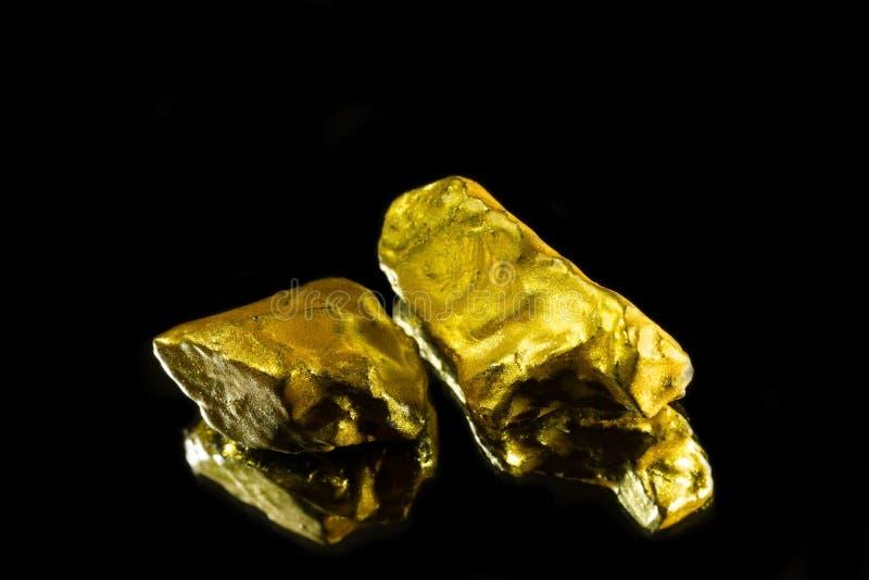 Złote bryłki odizolowywać na czarnym tle na lustra zakończeniu up obraz royalty free