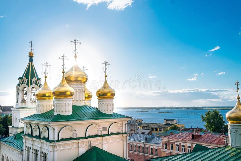 Złote kopuły z krzyżami na Ortodoksalnym kościół St John baptysta na tle niebieskie niebo i Volga rzeka, Rosja, Nizhny obraz stock