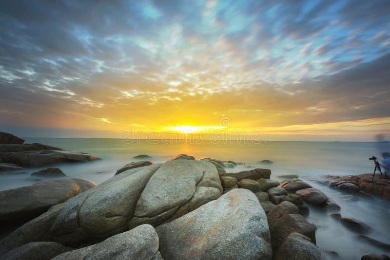 Złote krople morze fala która uderza skałę na zmierzchu obraz stock
