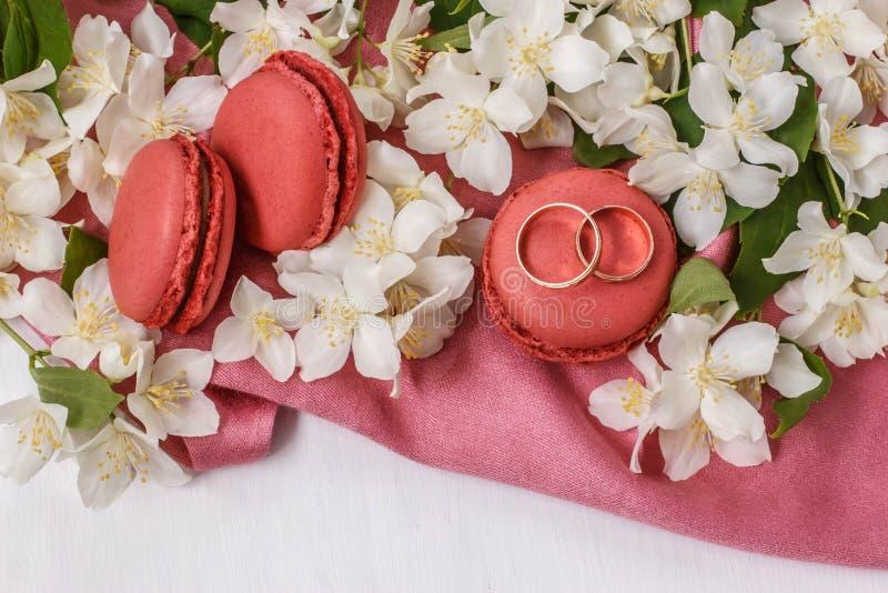 Złote obrączki ślubne z kwiatami jaśmin, macaroons i menchie biali, drapują obrazy stock