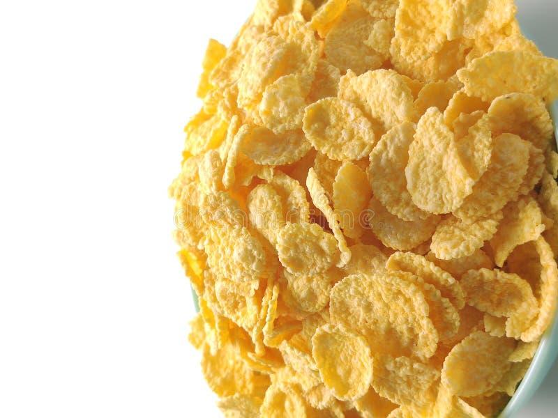 Złote płatki kukurydziane na białym tle w niebieskiej płytce zbliżenie fotografia stock