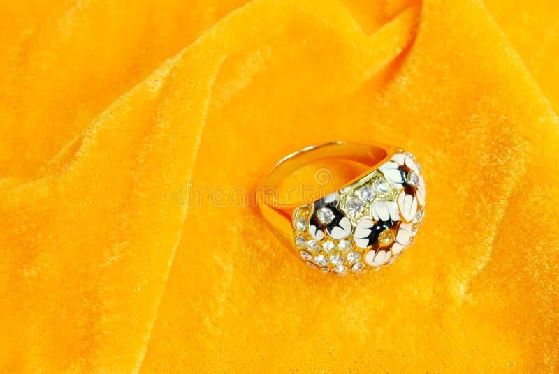 Złotego aksamitnego tła diamentowy pierścionek fotografia royalty free