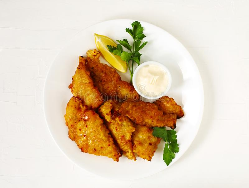 Złotego ciasta naleśnikowego głęboki smażący rybi przepasuje, słuzyć na bielu talerzu z kumberlandem i cytryną zdjęcie stock