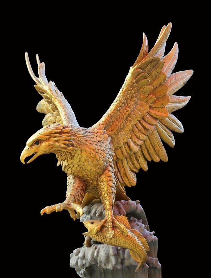 Złotego orła statua z dużymi rozprężonymi skrzydłami odizolowywającymi na czarnym tle fotografia royalty free