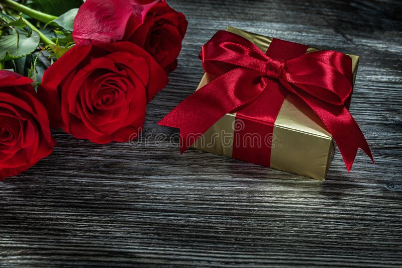 Złotego teraźniejszości pudełka czerwone róże na drewnianej desce obrazy stock
